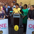 "Mayor Rawlings-Blake stands at a podium, surrounded by others holding signs that read ""One Baltimore"""